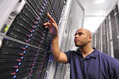 Strato Mitarbeiter in Rechenzentrum vor Server Rack